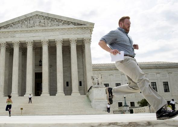 An intern runs to hand off a copy of the decision of Texas Department of Housing and Community Affairs v. Inclusive Communities Project at the Supreme Court on June 25, 2015.