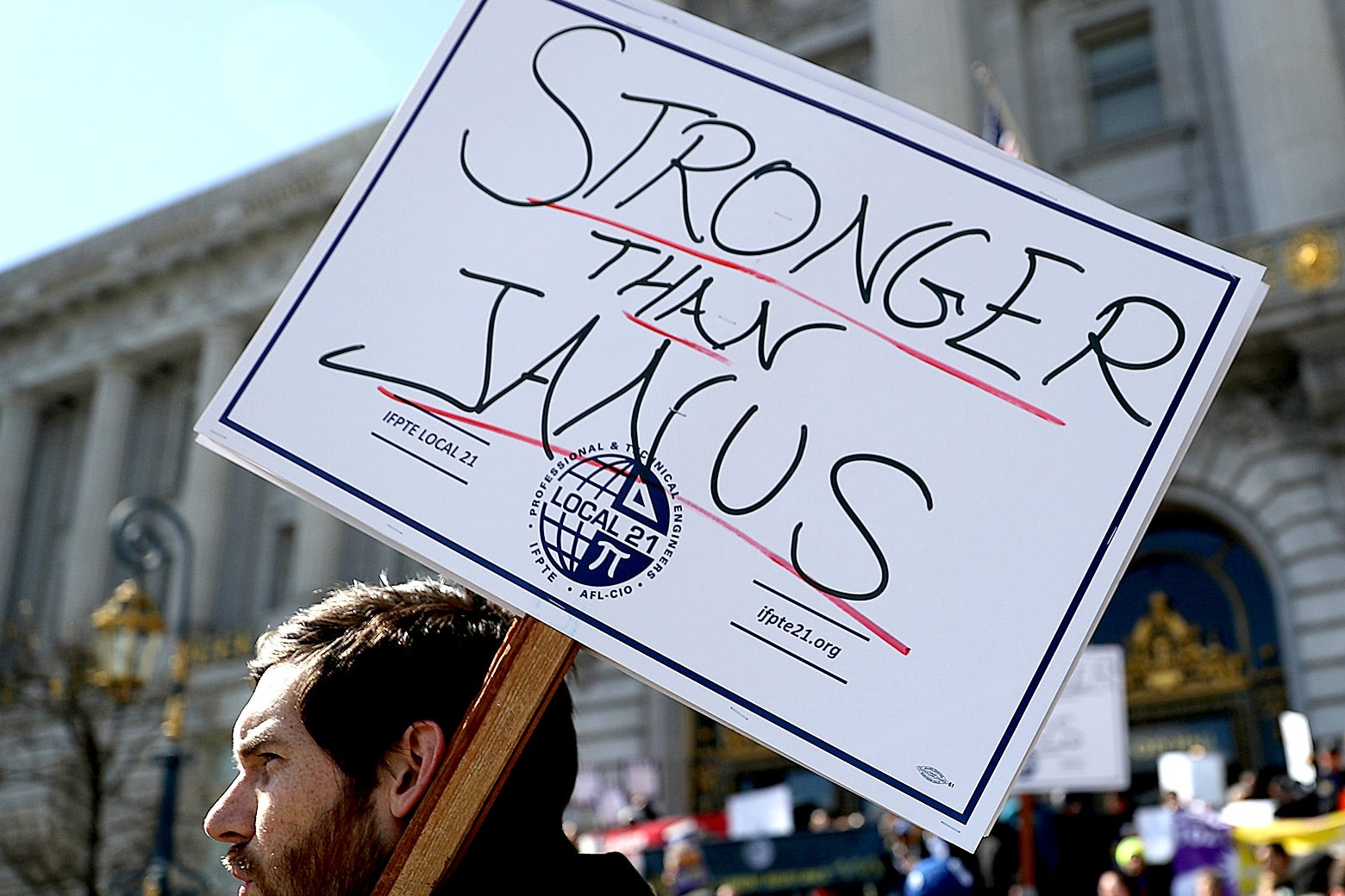 "A union member protesting outside San Francisco City Hall holds a sign reading ""STRONGER THAN JANUS."""