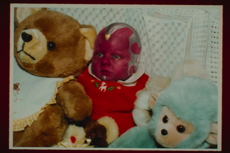 Baby Vision sits in a bed with some stuffed animals.