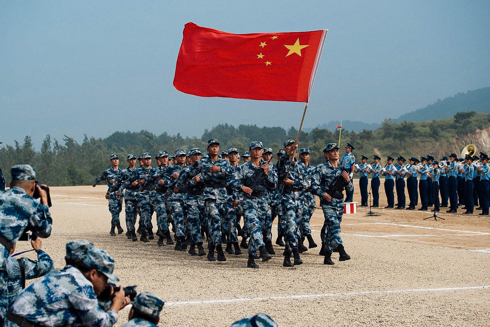 Uniformed Chinese troops march in formation with their national flag.