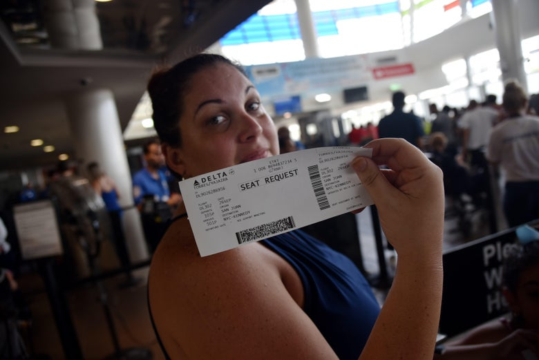 A woman shows her ticket for a seat request while waiting in a line at Luis Munoz Marin International Airport, in San Juan, Puerto Rico, on September 26, 2017, as some flights are still being rescheduled for one or two weeks. 