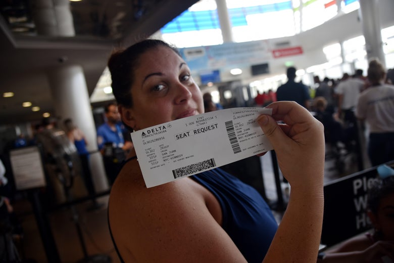 A woman shows her ticket for a seat request while waiting in a line at Luis Munoz Marin International Airport, in San Juan, Puerto Rico, on September 26, 2017, as some flights are still being rescheduled for one or two weeks.  The US island territory, working without electricity, is struggling to dig out and clean up from its disastrous brush with the hurricane, blamed for at least 33 deaths across the Caribbean. / AFP PHOTO / HECTOR RETAMAL        (Photo credit should read HECTOR RETAMAL/AFP/Getty Images)