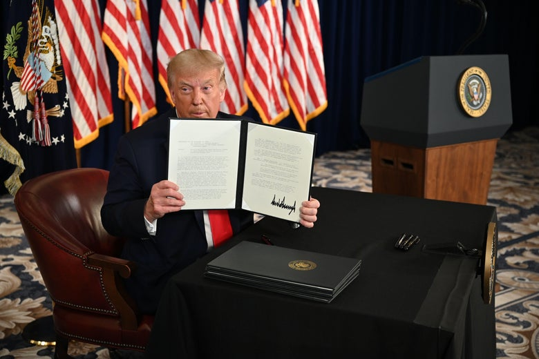 President Donald Trump holds up the executive order he signed.