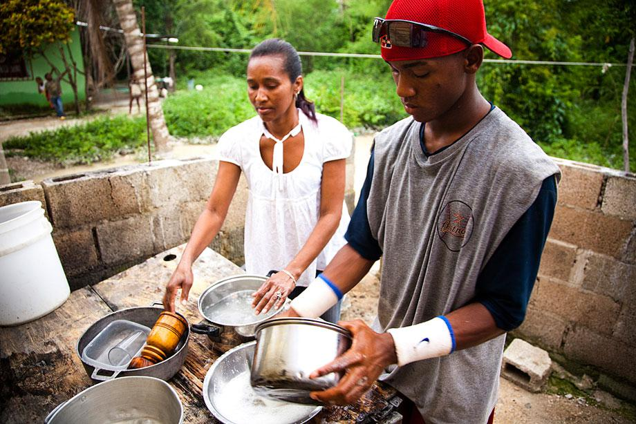 BOCA CHICA, DOMINICAN REPUBLIC. A portrait of a top prospect, Raymel Flores, who at this time was anxiously awaiting his 16.5 birthday when he was eligible to sign with an MLB team. His tiny home has a tin roof and leaks water throughout the year. Here, he washes dishes with his mother. A few weeks after this image was taken, Raymel signed with the Boston Red Sox for USD$900,000.