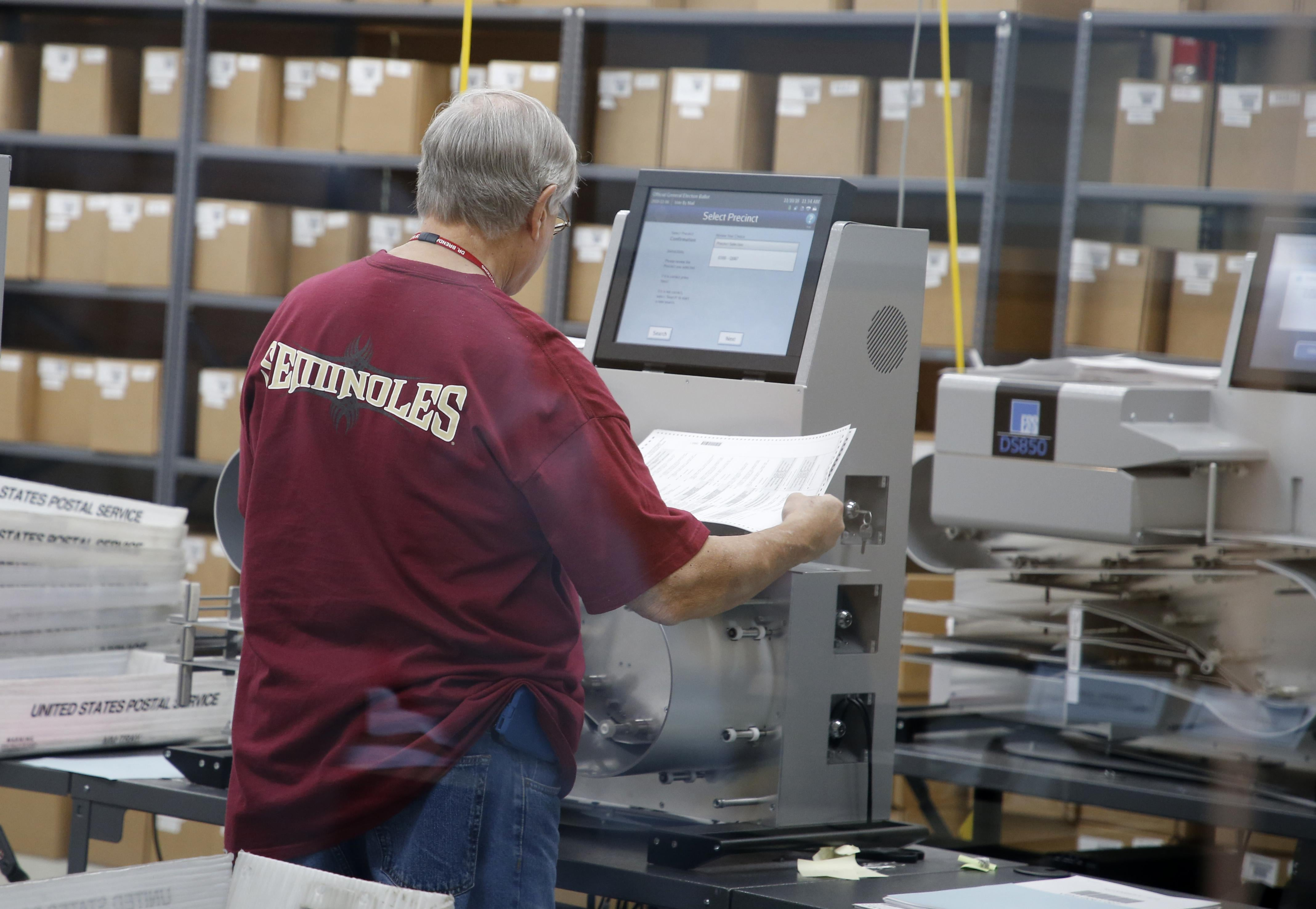 A worker feeds ballots into a tabulation machine, with many cardboard boxes on the shelves in the background.