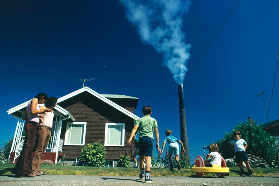 """Children play in yard of Ruston home, whileTacoma smelter stack showers area with arsenicand lead residue.""Gene Daniels, Ruston, Washington, August 1972"