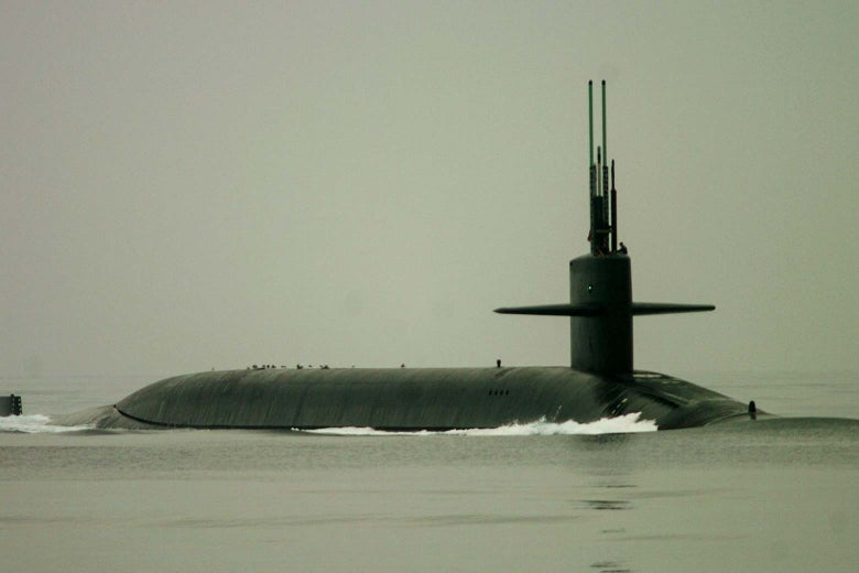 A submarine mostly submerged in water.