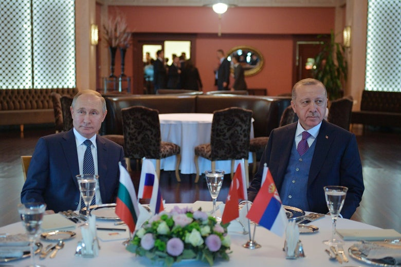 Russian President Vladimir Putin and Turkish President Recep Tayyip Erdogan sit at the same table looking away from one another during a meeting in Istanbul.