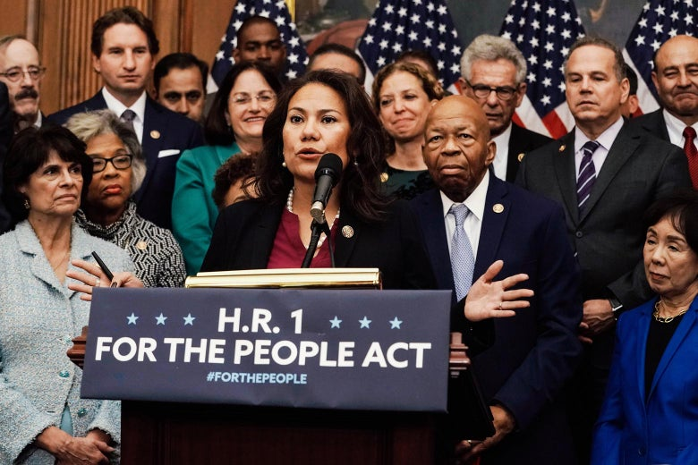 """Veronica Escobar speaks from behind a podium that says, """"H.R. 1: For the People Act,"""" surrounded by colleagues."""