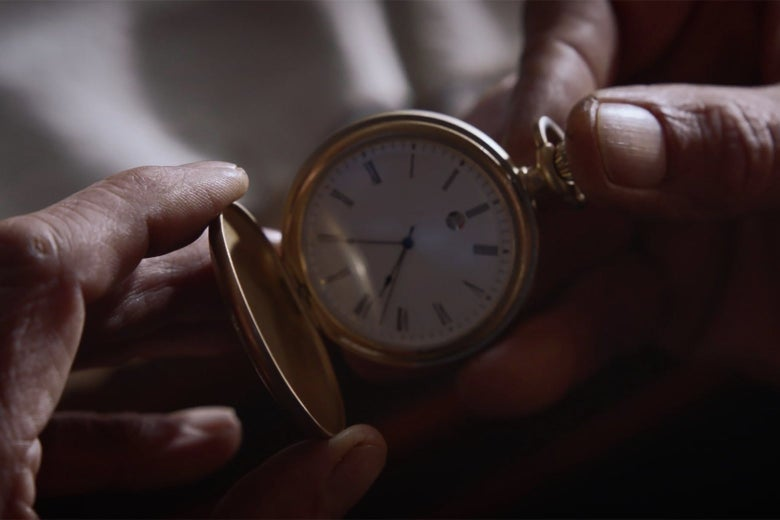 A man's hands hold a pocket watch in a still from Watchmen.