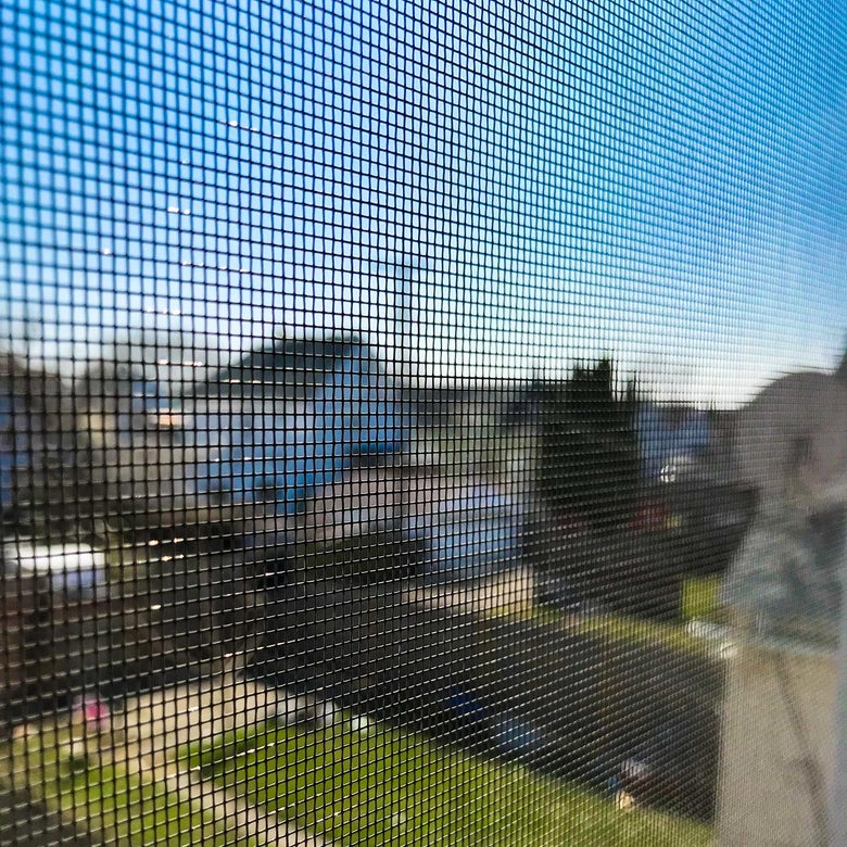 A window screen over a view of suburban backyards and homes