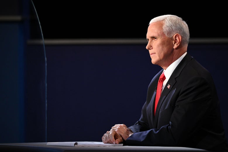Pence sits at his desk at the debate stage.