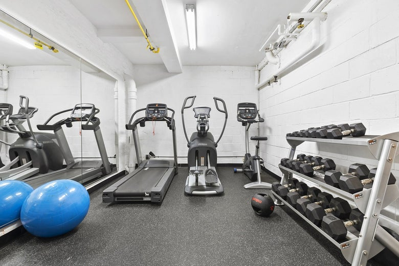 A small gym with weights, a treadmill, an exercise bike, and a stair climber