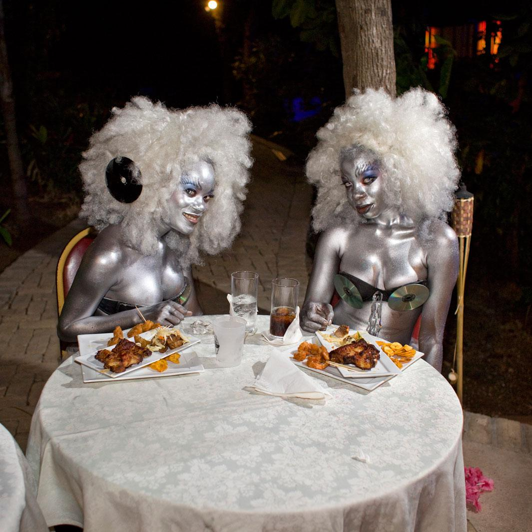 At the Karibe Hotel, above Port-au-Prince, two go-go girls dig into fried chicken after dancing for hours at the concert of a local singer, J Perry. Juvènat,  Pétion-ville, Haiti.