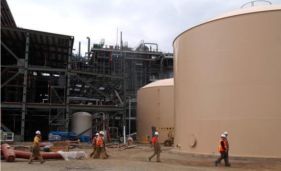 Construction workers walk by the demineralised and raw water tanks.
