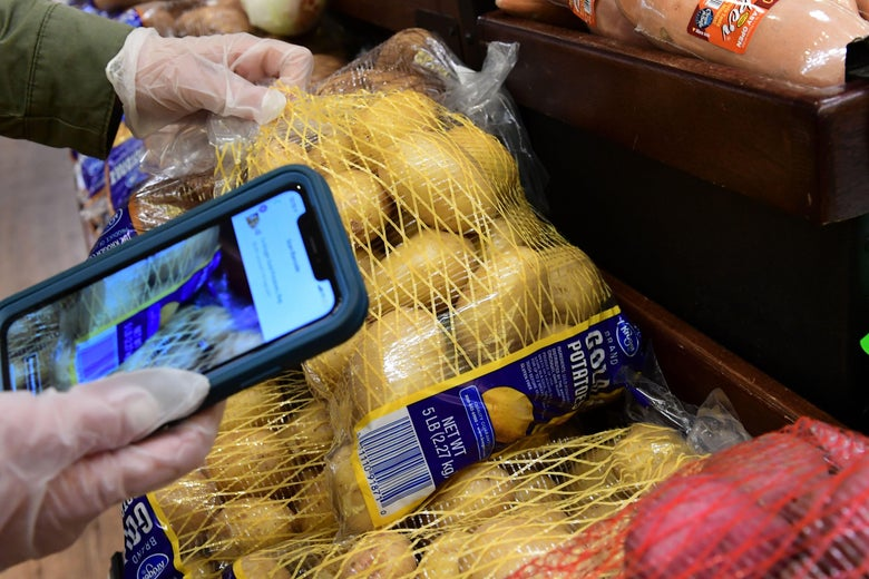 Gloved hands of an Instacart employee using a cellphone to scan barcodes while picking up groceries