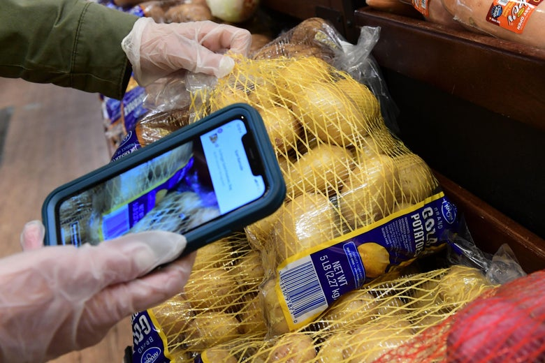 An Instacart employee uses a cellphone to scan barcodes while picking up groceries from a supermarket for delivery on March 19, 2020 in North Hollywood, California.