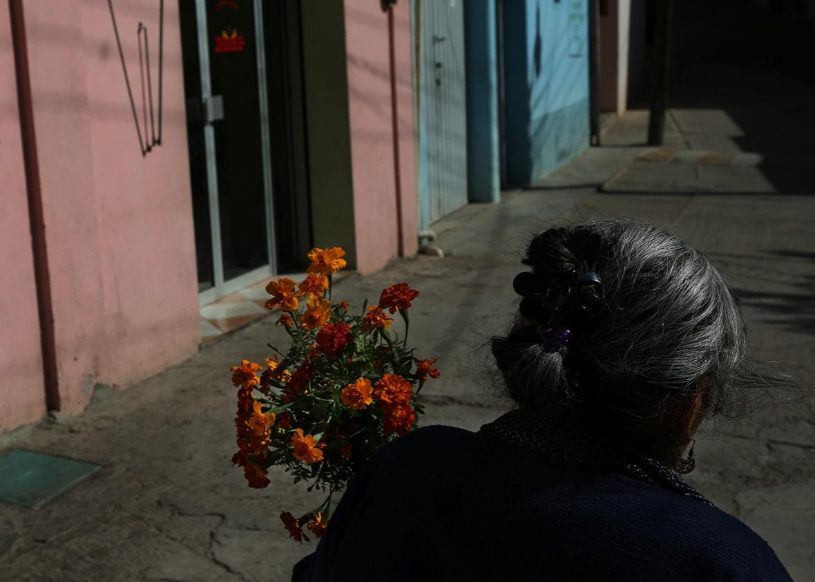 Teresa Raymundo walks to a funeral with a bundle of flowers in San Juan del Rio, Oaxaca, Mexico.