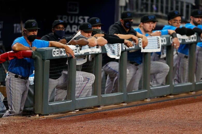 A row of Marlins players, some wearing masks and some not, stand against the fence at the edge of their dugout.