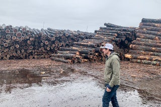 Alden Robbins stands in front of tall piles of logs on a cloudy day
