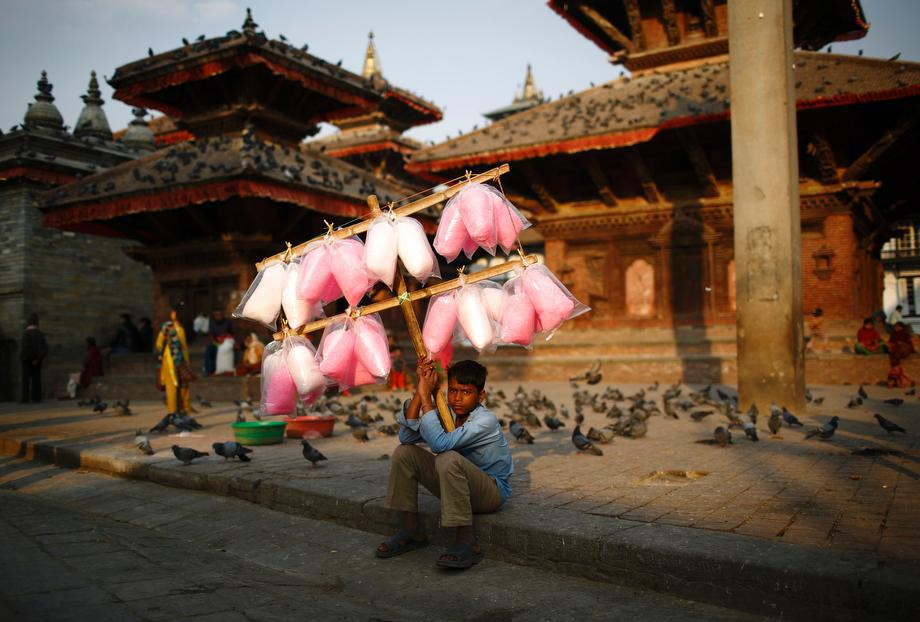 Satrohan Kumar Sahani, 12, sells cotton candy as he waits for customers along the street at Hanumandhoka Durbar Square in Kathmandu, Nepal on March 18, 2013.