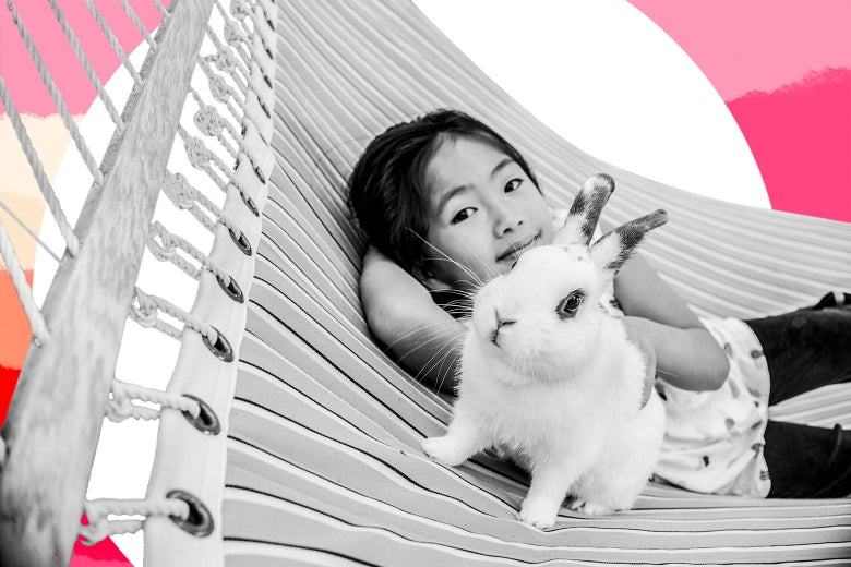 A girl smiles beside her extremely realistic stuffed rabbit on a hammock.