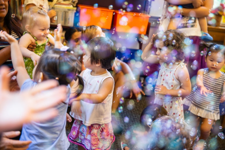 Children play amid bubbles.