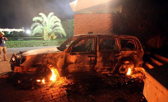 A vehicle sits smoldering in flames after being set on fire inside the US consulate.