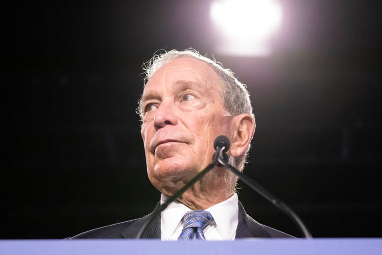 Bloomberg, standing at a blue lectern, looks to his right against a black backdrop.