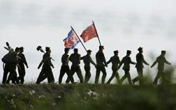 North Korean soldiers carrying the North Korean flag.