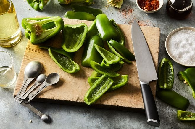 Sliced green peppers on a cutting board.
