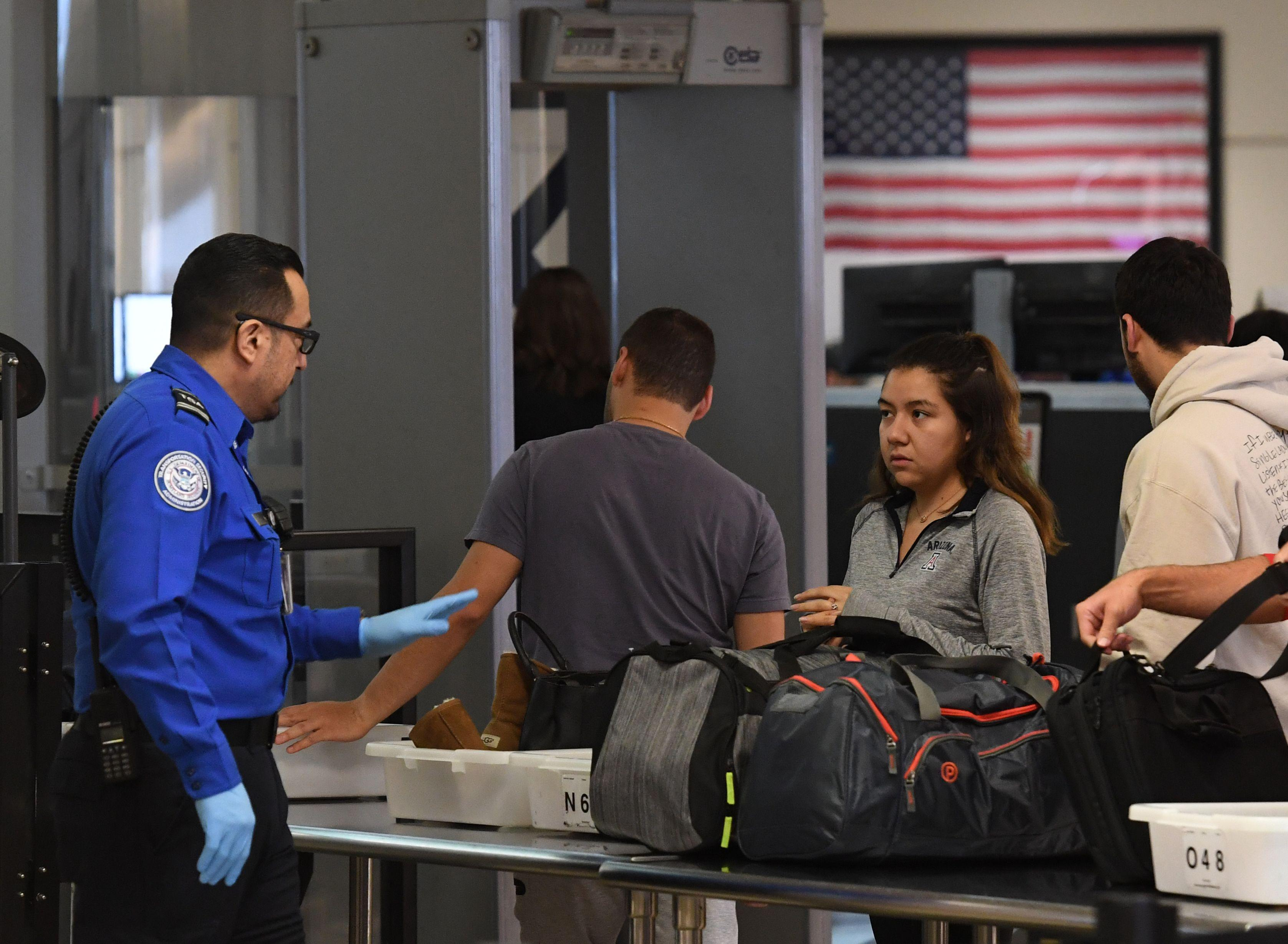 Transportation Security Administration (TSA) officers work unpaid on the first day of the partial government shutdown, at LAX Airport in Los Angeles, California on December 22, 2018.