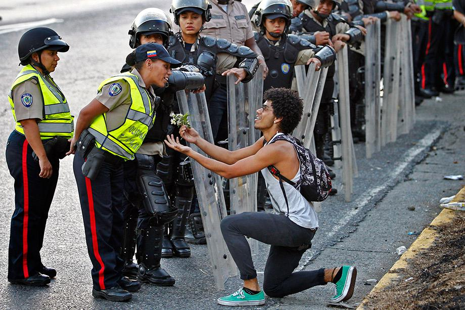 An opposition demonstrator gives flowers to a police officer as demonstrators block the city's main highway during a protest against Nicolas Maduro's government in Caracas.