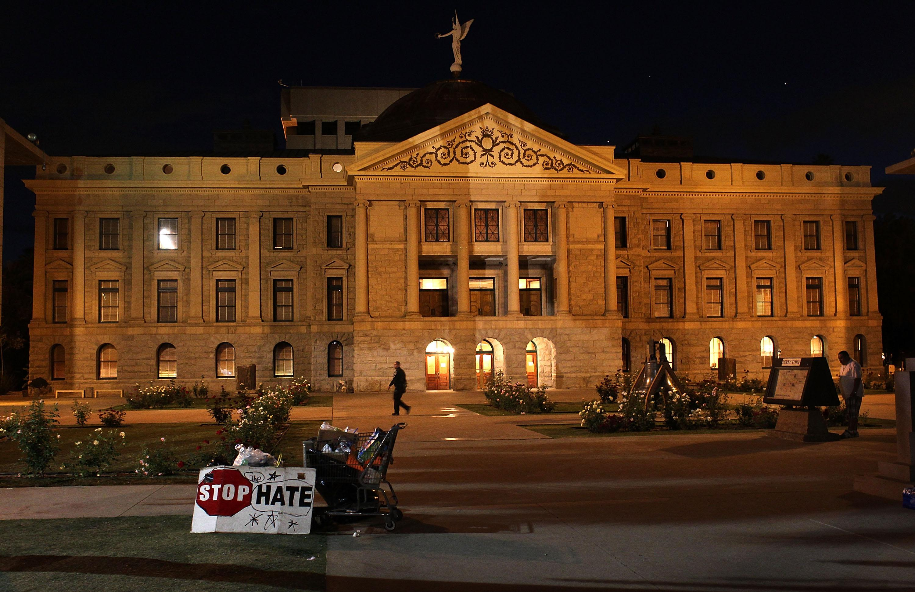 "A sign saying ""stop hate"" can be seen in front of a capitol building at night"