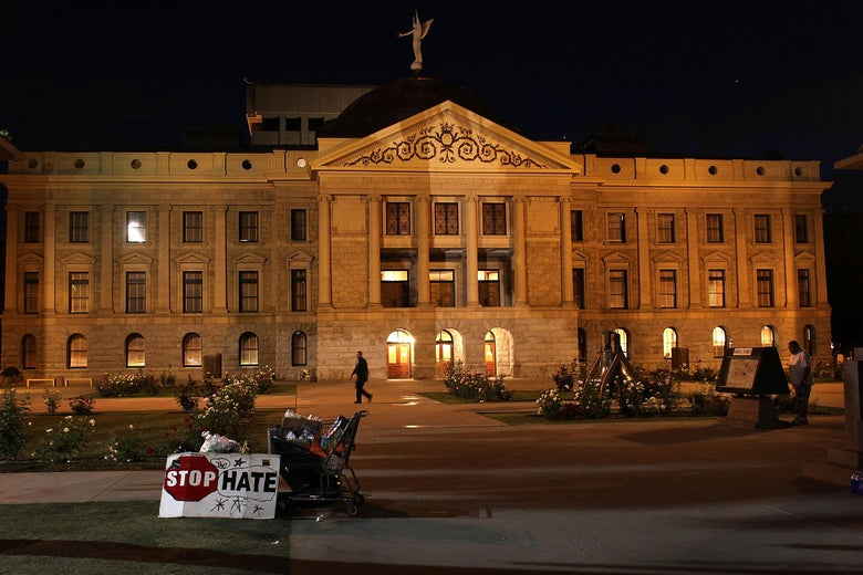 """A sign saying """"stop hate"""" can be seen in front of a capitol building at night"""