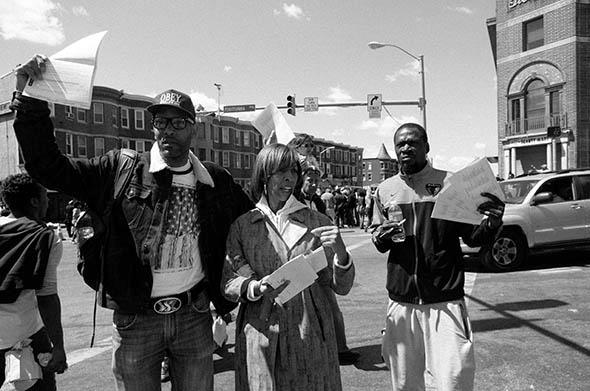 Maryland State Sen. Catherine Pugh stands with two young men handing out voter registration forms and pens to complete them with, Baltimore.