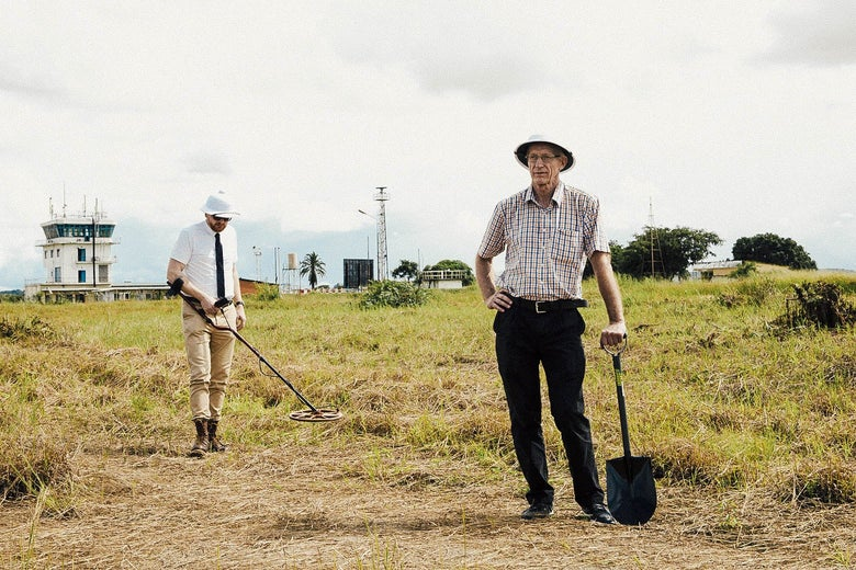 Mads Brügger and Göran Björkdahl standing in a field wearing white helmets. Brügger is wielding what looks like a metal detector, and Björkdahl leans on a shovel.