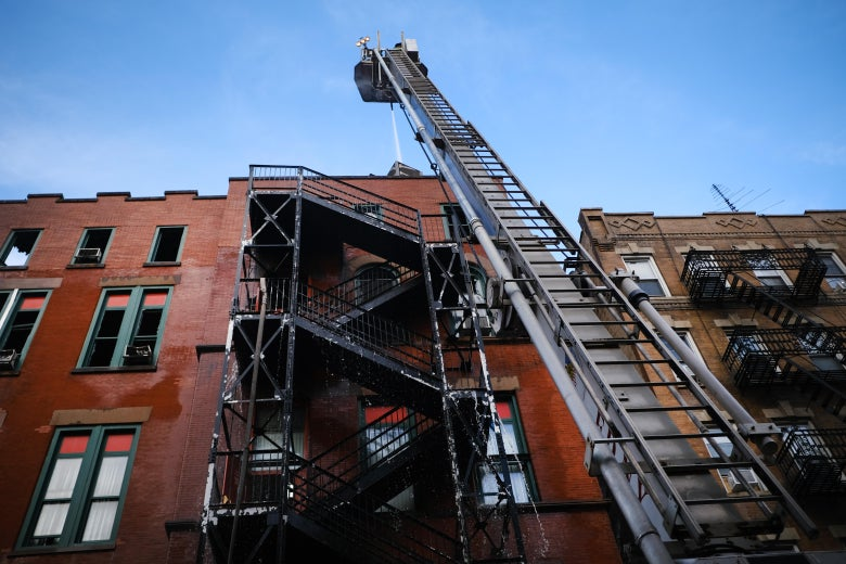 The building, as seen from below. A fire truck's ladder has been extended to an upper floor.