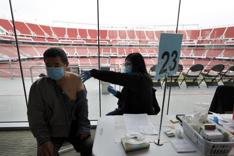 A man getting a shot in his arm outside a stadium.