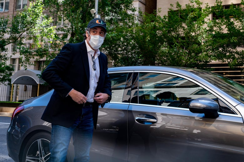 Michael Cohen is seen wearing a face mask next to a car.