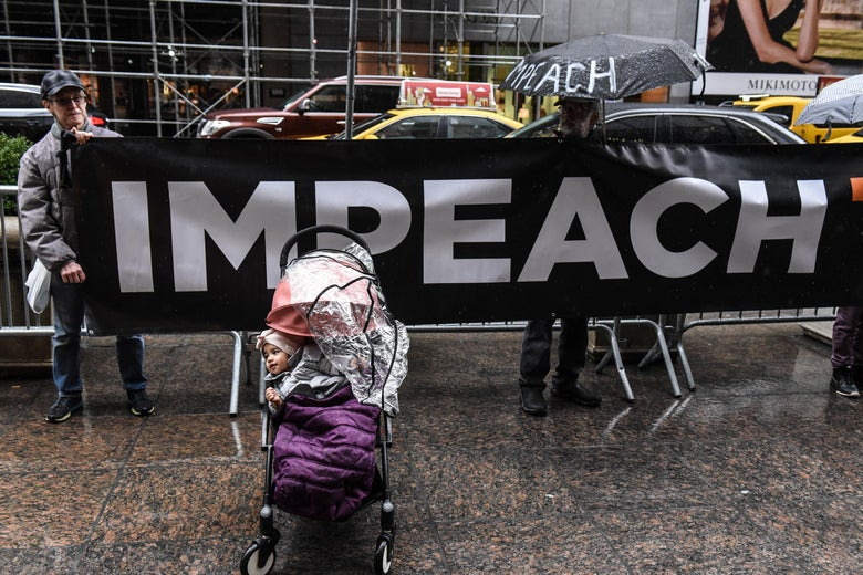 "A baby sits in a stroller in front of a sing that reads ""impeach"" while a protest group called Rise and Resist holds a protest in front of Trump Tower demanding that The Trump Organization executives ""cooperate with Congress"" on March 21, 2019 in New York City."