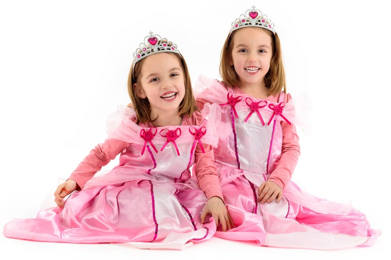 Two little girls dressed in pink princess outfits.