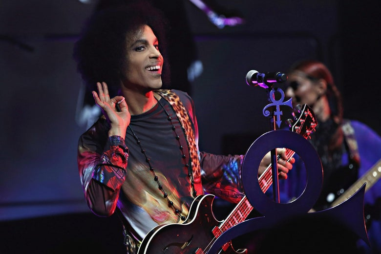 A man with a large afro and wearing a multi-colored suit holds a guitar on a stage. He leans to the right side of the microphone with his hand by his ear, smiling.