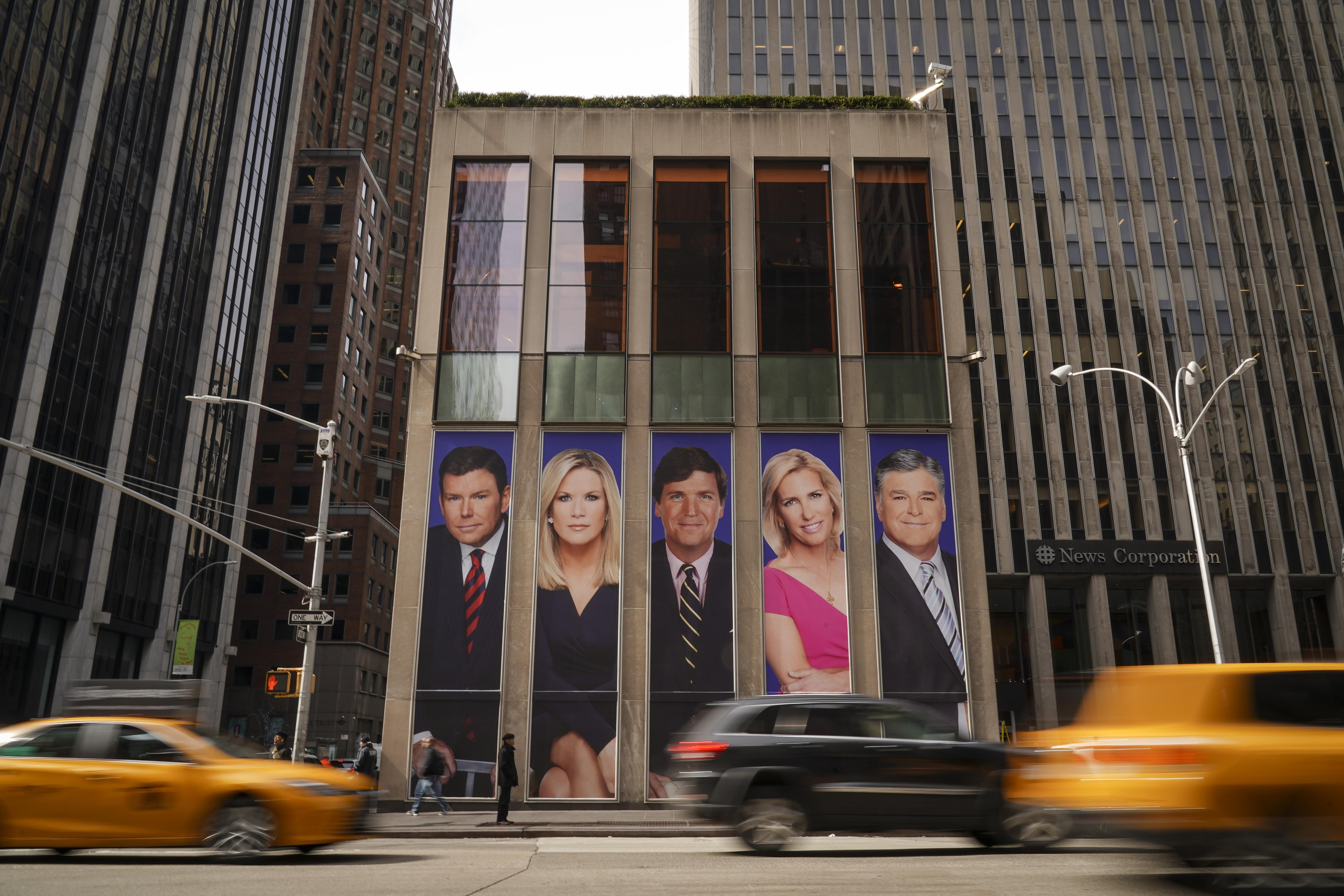 Traffic on Sixth Avenue passes by advertisements featuring Fox News personalities, including Bret Baier, Martha MacCallum, Tucker Carlson, Laura Ingraham, and Sean Hannity, adorn the front of the News Corporation building, March 13, 2019 in New York City. On Wednesday the network's sales executives are hosting an event for advertisers to promote Fox News. Fox News personalities Tucker Carlson and Jeanine Pirro have come under criticism in recent weeks for controversial comments and multiple advertisers have pulled away from their shows. (Photo by Drew Angerer/Getty Images)