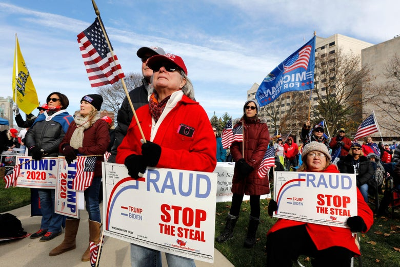 """A crowd of Trump supporters holding """"Stop the Steal"""" and """"Trump 2020"""" signs and American flags"""