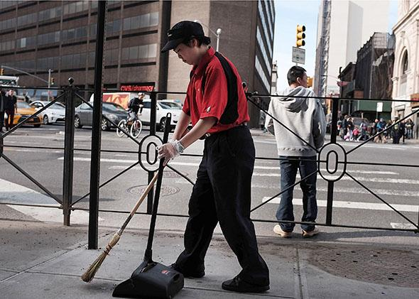 A McDonald's employee sweeps up in front of a restaurant.