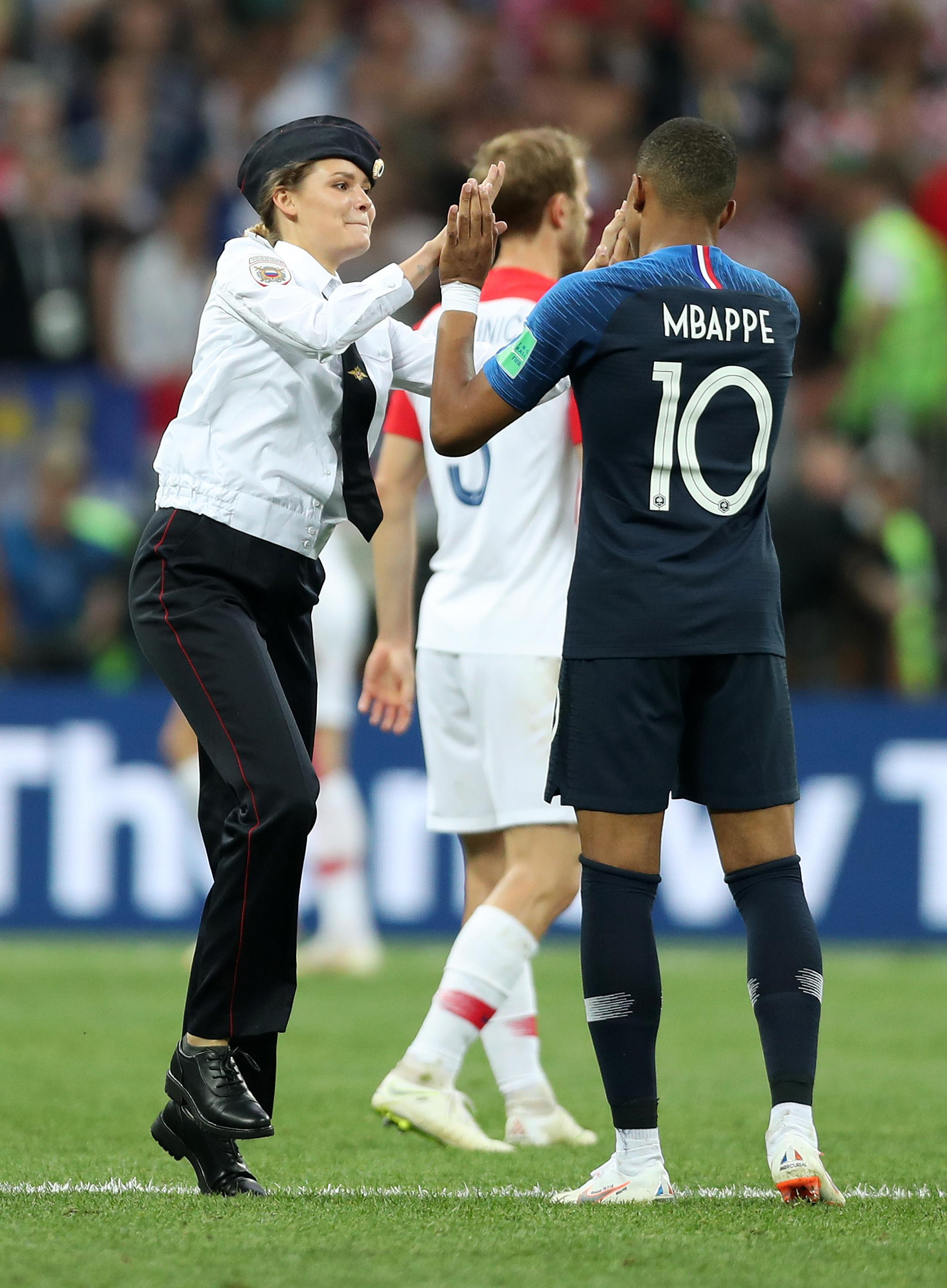 A pitch invader high fives Kylian Mbappe of France during the 2018 FIFA World Cup Final between France and Croatia at Luzhniki Stadium on July 15, 2018 in Moscow, Russia.