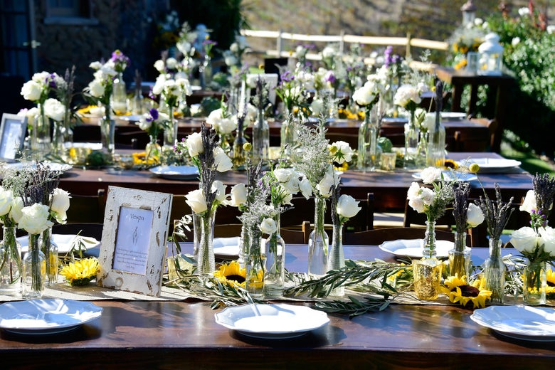 Flowers in vases and porcelain plates sit on dark wooden benches at an outdoor wedding