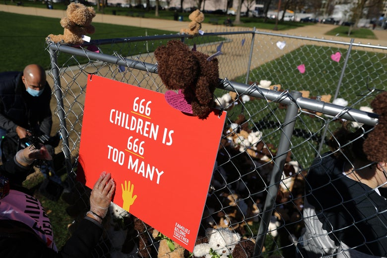 "A cage full of teddy bears with a sign on it that says ""666 children is 666 too many"""