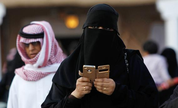 A woman using an iPhone visits the 27th Janadriya festival on the outskirts of Riyadh February 13, 2012. The two-week-long festival showcases Saudi Arabian culture and traditions.